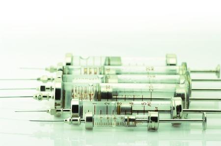 toned image: Set of glass syringes on light background. Toned image.