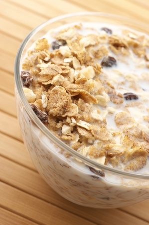 Close-up of muesli with milk in glass bowl on wooden surface. Stock Photo - 8584751