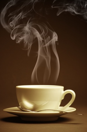 Cup of hot coffee with steam on dark background. Toned image. photo