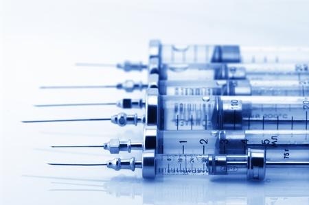 surgical tool: Set of glass syringes on light background. Toned image.