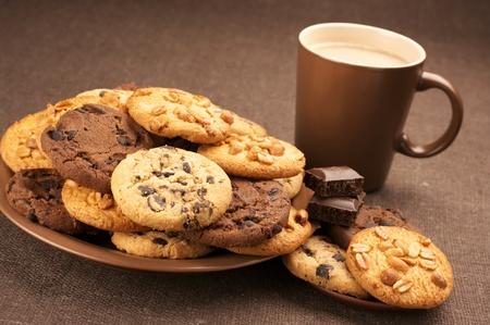 Assorted cookies in bruin plaat en bruin mok van koffie op bruin doek.