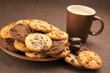 Assorted cookies in brown plate and brown mug of coffee on brown canvas. photo