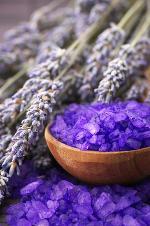 Violet bath salt in wooden spoon and bunch of dried lavender on brown mat. Stock Photo - 8708650