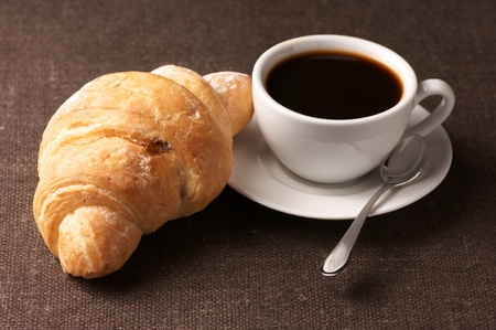 french bread rolls: Croissant and white cup of black coffee on brown canvas. Stock Photo