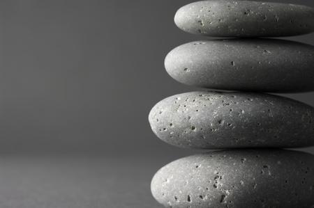 Stack of grey massage stones on dark grey background. photo