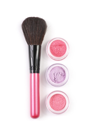 Pink make-up brush and powder eye shadows in jars isolated on white background. photo