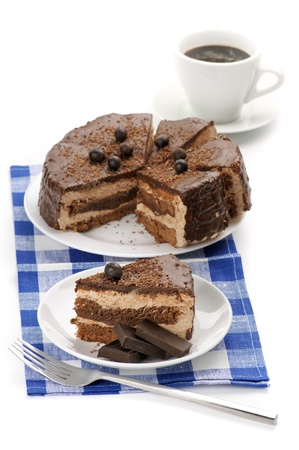 Homemade chocolate cake in white plates and coffee on blue checked napkin. photo