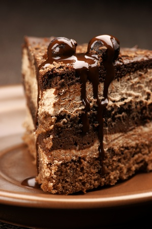 layer cake: Close-up of homemade chocolate cake in brown ceramic plate. Stock Photo