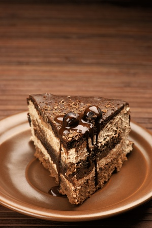 Homemade chocolate cake in brown ceramic plate on brown wooden surface. photo