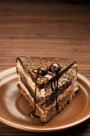 porcion de torta: Pastel de chocolate casero en placa cerámica marrón en la superficie de madera marrón. Foto de archivo