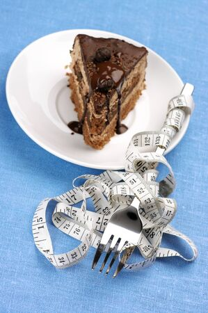 Piece of chocolate cake and measuring tape wrapped around fork on blue background. photo