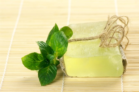 Bar of natural handmade soap with mint on wooden mat. Stock Photo - 8903673