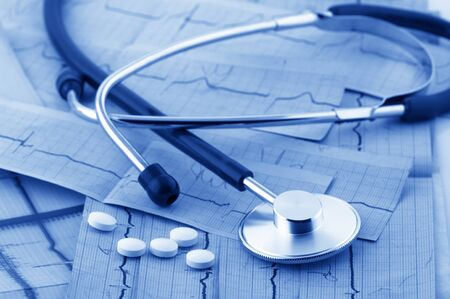 medical help: Close-up of stethoscope and pills on cardiograms. Monochrome blue toned image. Stock Photo
