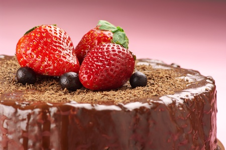 an icing: Close-up of homemade chocolate cake with strawberries on pink background. Stock Photo