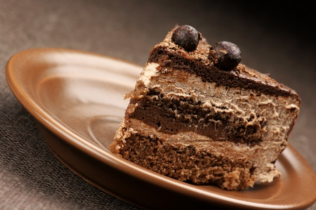 Close-up of homemade chocolate cake in brown ceramic plate. Stock Photo