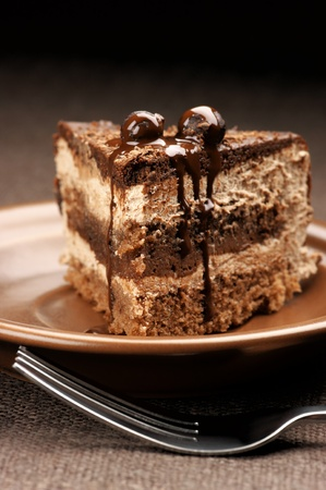 Close-up of homemade chocolate cake in brown ceramic plate. photo