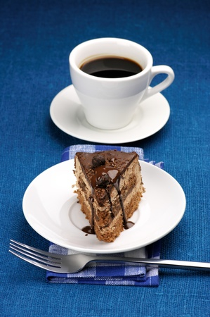 Piece of chocolate cake in white plate and white cup of coffee on blue background. Stock Photo - 9098970