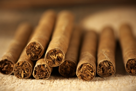 Heap of cigars on old wooden surface. photo