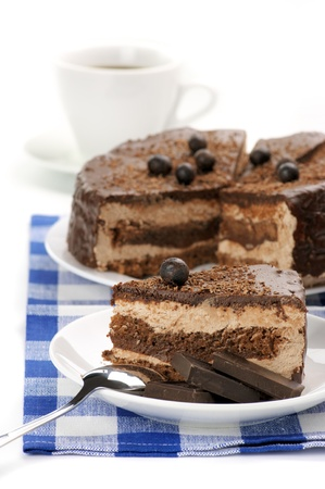 Close-up of homemade chocolate cake in white plates and coffee on blue checked napkin. photo
