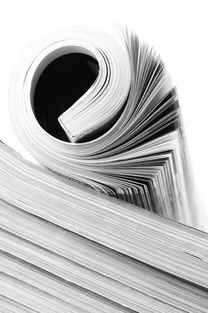 periodical: Rolled magazine on magazine stack. B&W image. Stock Photo