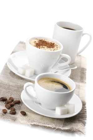 Three white cups of assorted coffee on linen napkin against white background. Stock Photo - 9294635