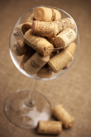 Heap of used vintage wine corks in wineglass on burlap. Stock Photo - 9347235