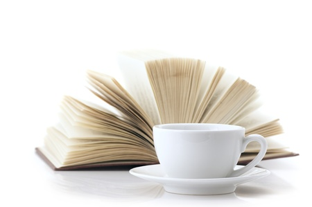 White cup of coffee and open book isolated on white background. photo