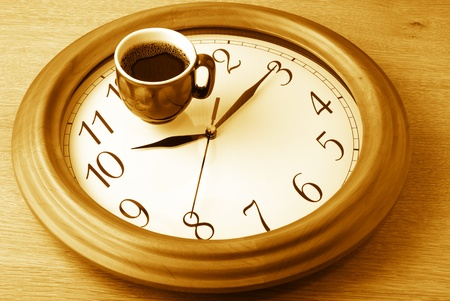 coffee hour: Coffee time: cup of coffee on clock dial. Monochrome toned image.