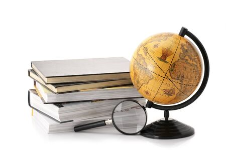 Vintage globe, stack of books and magnifier isolated on white background. photo
