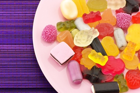 bonbons: Assorted colorful candy in pink plate on violet bamboo mat. Stock Photo