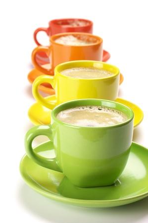 cerámicas: Cuatro copas coloridos con café fresco sobre fondo blanco.