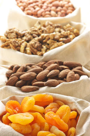 apricot kernels: Close-up of assorted nuts and dried apricots in jute bags.