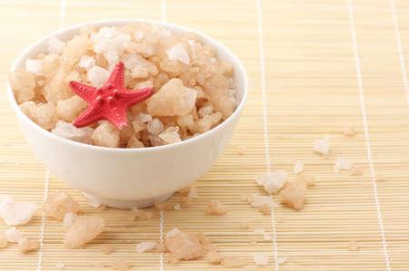 Peach-colored bath salt with starfish in white ceramic bowl on mat. photo