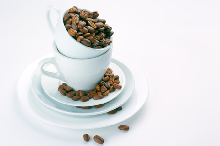 Roasted coffee beans in white cups on light background. Stock Photo - 9450797