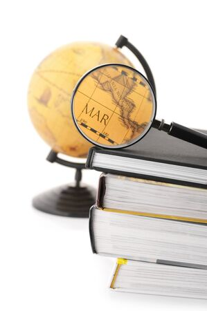 Stack of books, magnifier and vintage globe on white background. photo