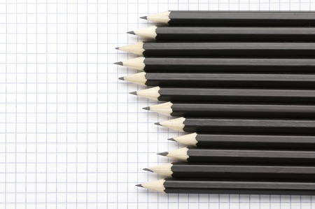 Set of black pencils on checked page. photo