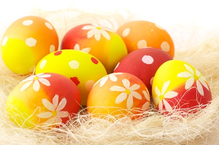 haulm: Yellow, orange and red Easter eggs in haulm on white background.