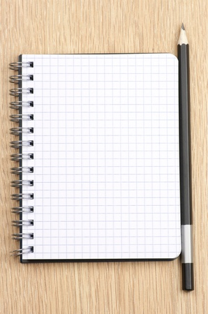 Spiral notepad with blank page and pencil on wooden desk. View from above. Stock Photo - 9450840