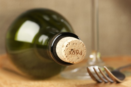 Closed wine bottle and wineglass in background. photo