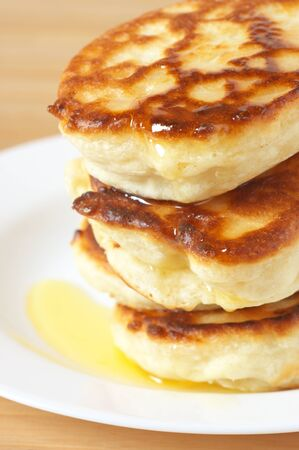 Stack of pancakes with honey close-up on white plate. photo