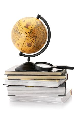 Vintage globe on stack of books and magnifier isolated against white background. photo