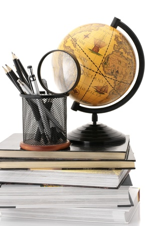 Vintage globe on stack of books and office supplies against white background. photo