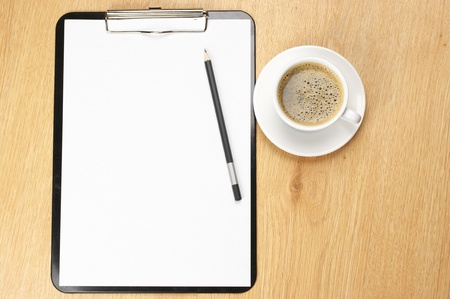 Clipboard with blank page and cup of coffee on wooden desk. View from above. Stock Photo - 9490937