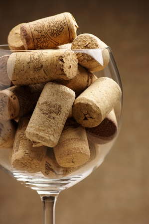 brown cork: Heap of used vintage wine corks in wineglass close-up.