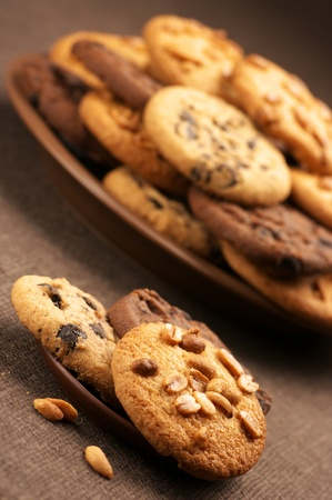 Heap of assorted cookies in brown plate and saucer on brown canvas. photo