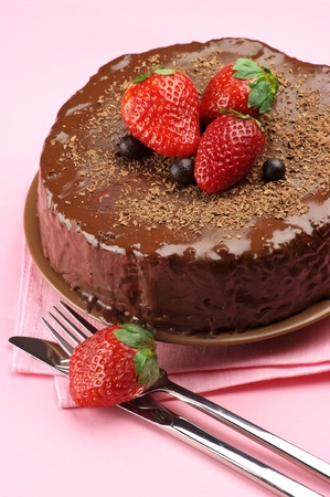 Homemade chocolate cake with strawberries, fork and knife on pink background.