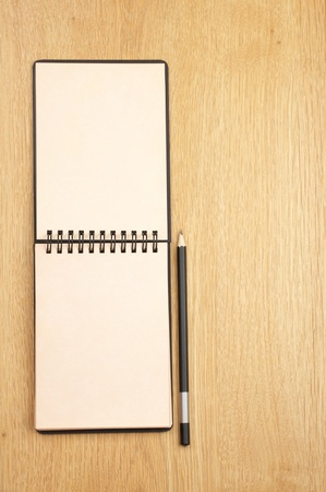 Notepad with blank pages and pencil on wooden desk. View from above. Stock Photo - 9524773