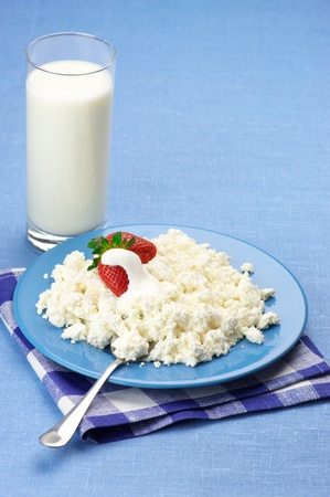 Cottage cheese with strawberries and cream in blue plate and glass of milk on blue tablecloth. photo