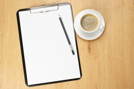 Clipboard with blank page and cup of coffee on wooden desk. View from above. Stock Photo - 9569310