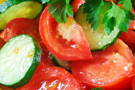slice tomato: Close-up of fresh salad of tomatoes, cucumbers and parsley. Full frame.
